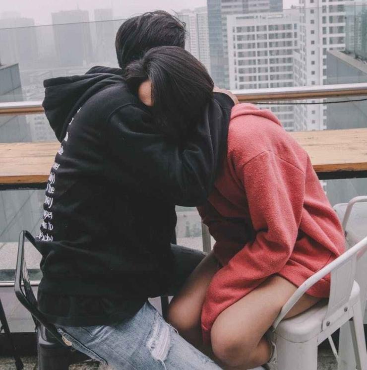 man hugging woman sitting on chair